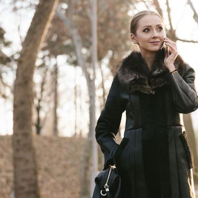 「待ち合わせ場所から電話する女性」の写真素材