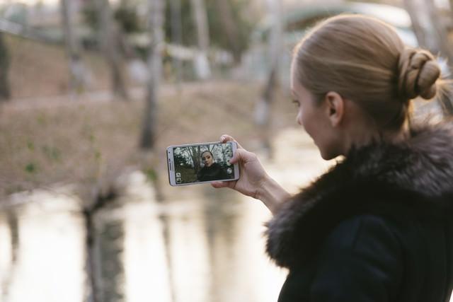 スマホで自撮りするブロンドの外国人女性の写真