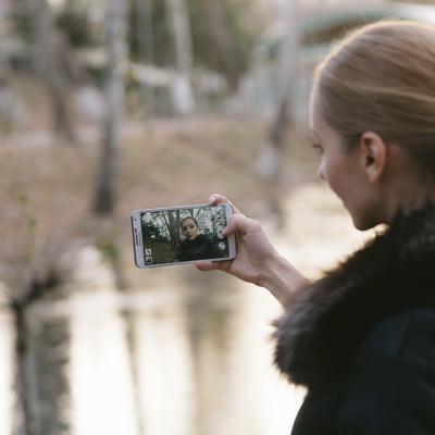 「スマホで自撮りするブロンドの外国人女性」の写真素材