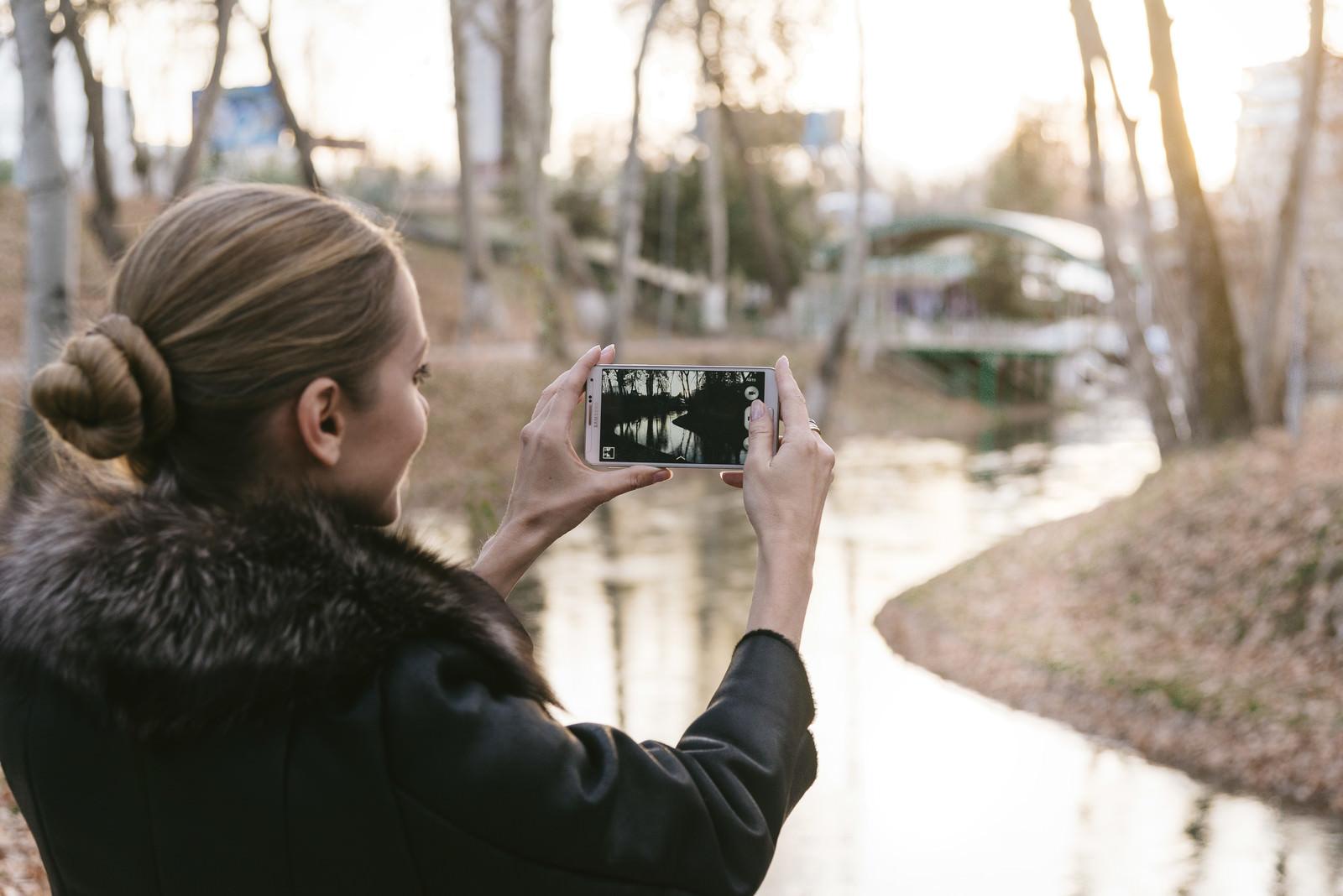 「スマートフォンで景色を撮影するブロンド美女」の写真[モデル:モデルファクトリー]