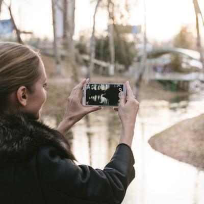 「スマートフォンで景色を撮影するブロンド美女」の写真素材