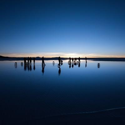 ウユニ塩湖の日の出を待つ人の写真
