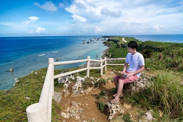 東平安名崎を一望しながらノマド中の男性の写真