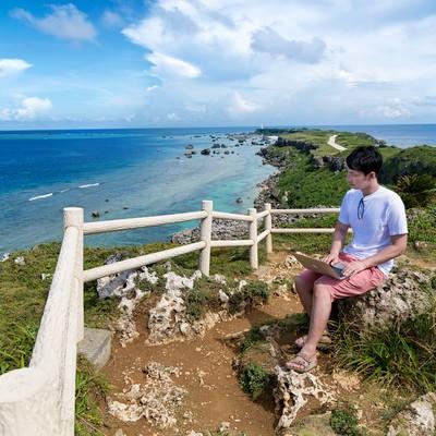 「東平安名崎を一望しながらノマド中の男性」の写真素材