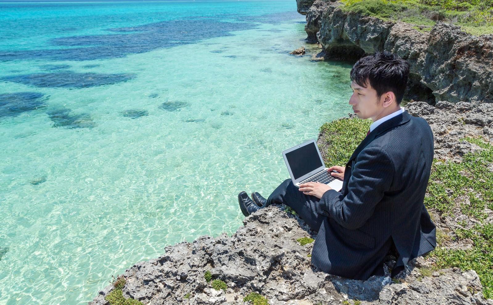 「シュノーケリングスポットでスーツを着用し請求書を作成するビジネスマン」[モデル:大川竜弥]