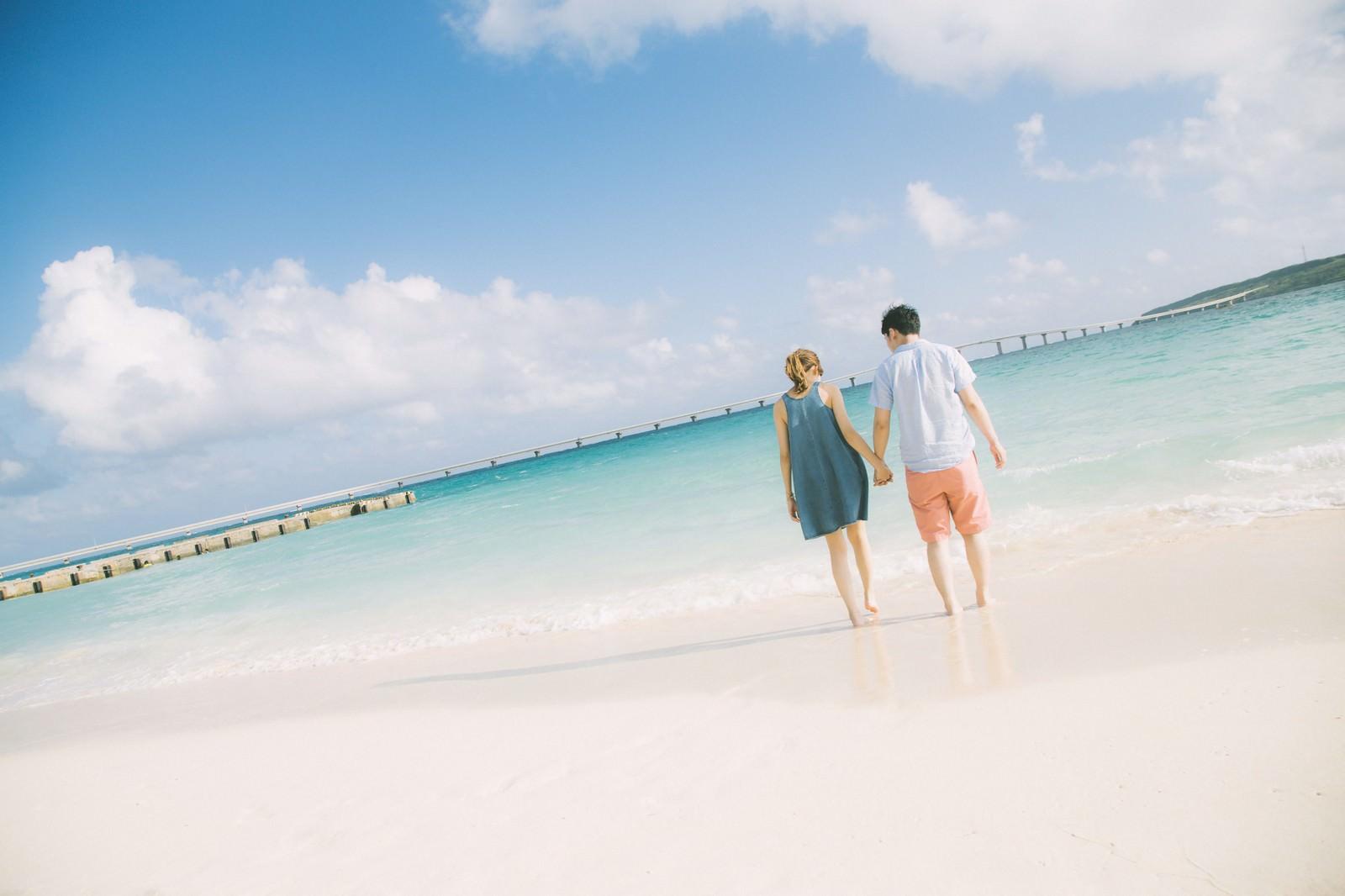 「来間大橋を見ながら、前浜ビーチで手を握りあうカップル | 写真の無料素材・フリー素材 - ぱくたそ」の写真