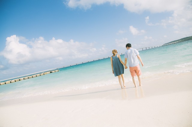 来間大橋を見ながら、前浜ビーチで手を握りあうカップルの写真