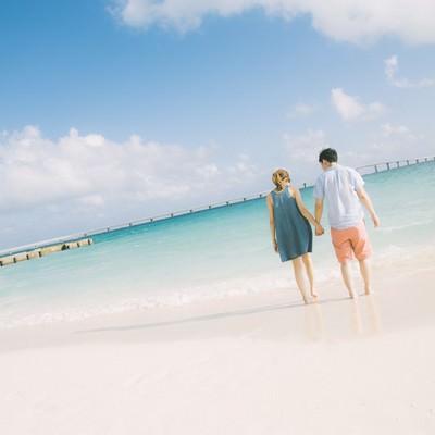 「来間大橋を見ながら、前浜ビーチで手を握りあうカップル」の写真素材