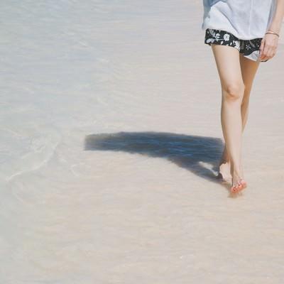 「日傘をさして砂浜を歩く女性の足元」の写真素材