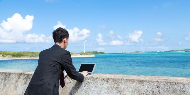 防波堤にMacBook Airを置き、打ち合わせをするノマドファイターの写真