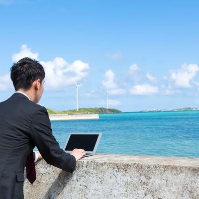 「防波堤にMacBook Airを置き、打ち合わせをするノマドファイター」の写真素材