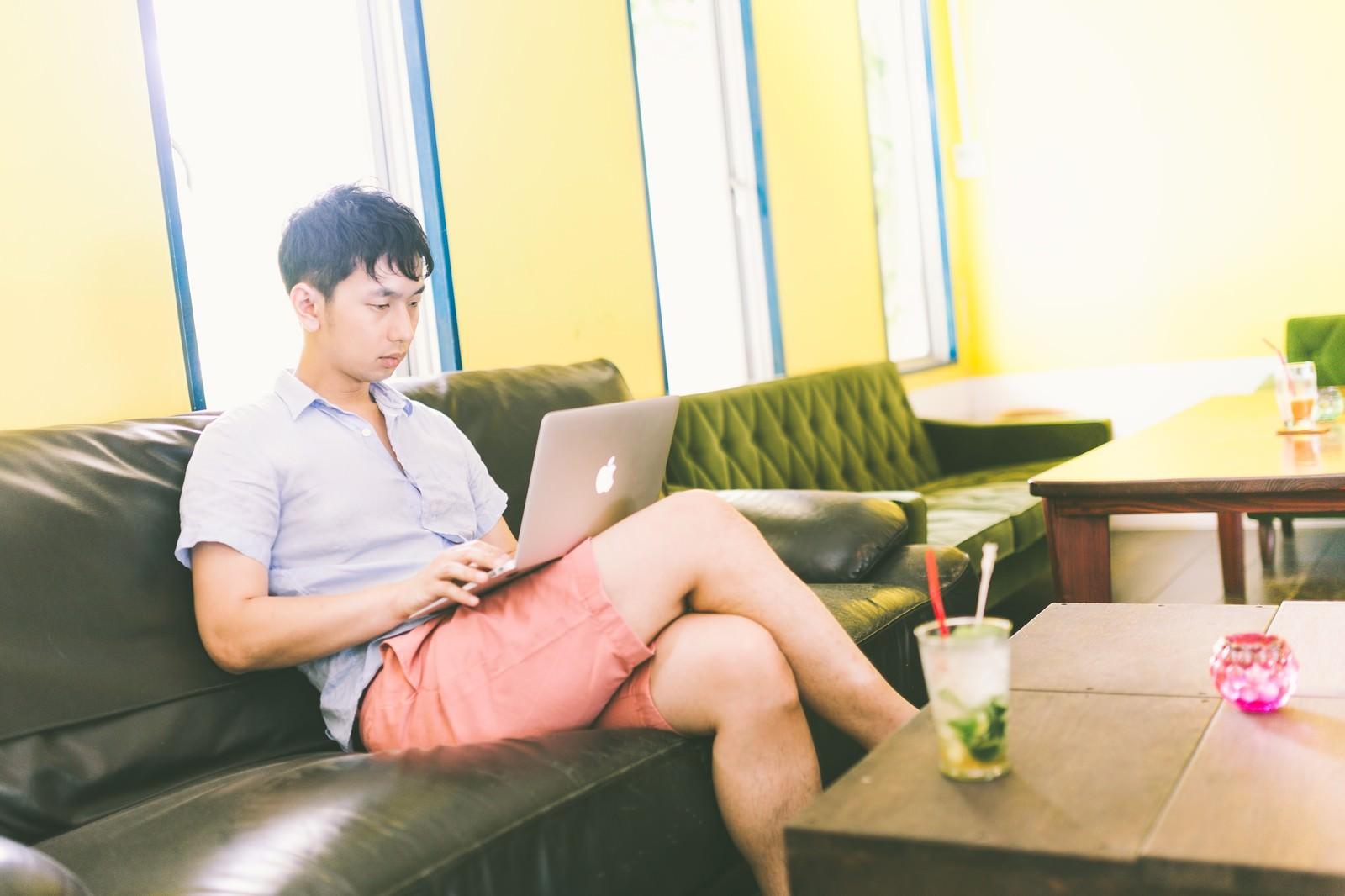 「コワーキングカフェで動画コンテンツを真剣に試聴する男性」の写真[モデル:大川竜弥]