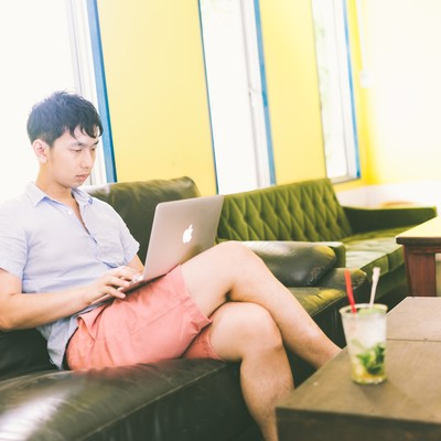 「コワーキングカフェで動画コンテンツを真剣に試聴する男性」の写真素材
