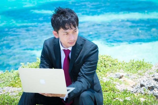 青い海をバックにMBAで作業を行うビジネスマンの写真