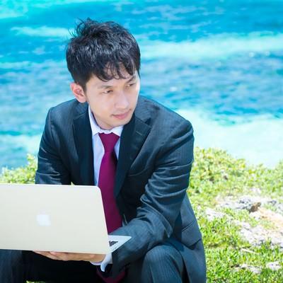 「青い海をバックにMBAで作業を行うビジネスマン」の写真素材