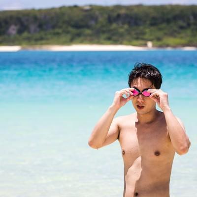 「度付きのゴーグルでビーチの水着ギャルを凝視する男性」の写真素材