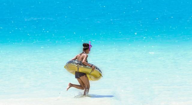 シュノーケリングセットと浮き輪を持って、海に駆け出すこんがり焼けた女の子の写真