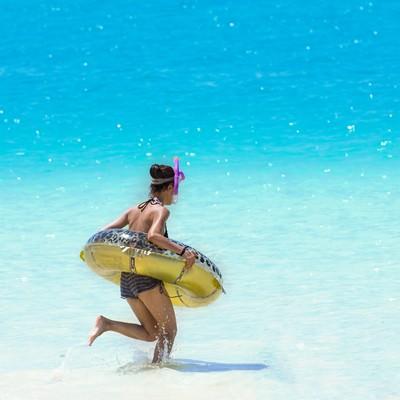 「シュノーケリングセットと浮き輪を持って、海に駆け出すこんがり焼けた女の子」の写真素材