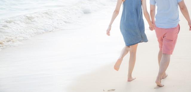 砂浜に思い出と足跡を残すいい雰囲気の男女の写真