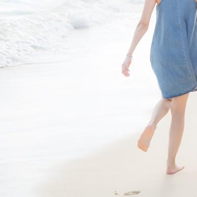 「砂浜に思い出と足跡を残すいい雰囲気の男女」の写真素材