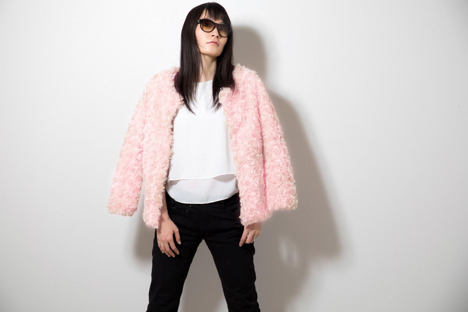 「ピンク色のプードルコートを着た女性」の写真[モデル:たけべともこ]