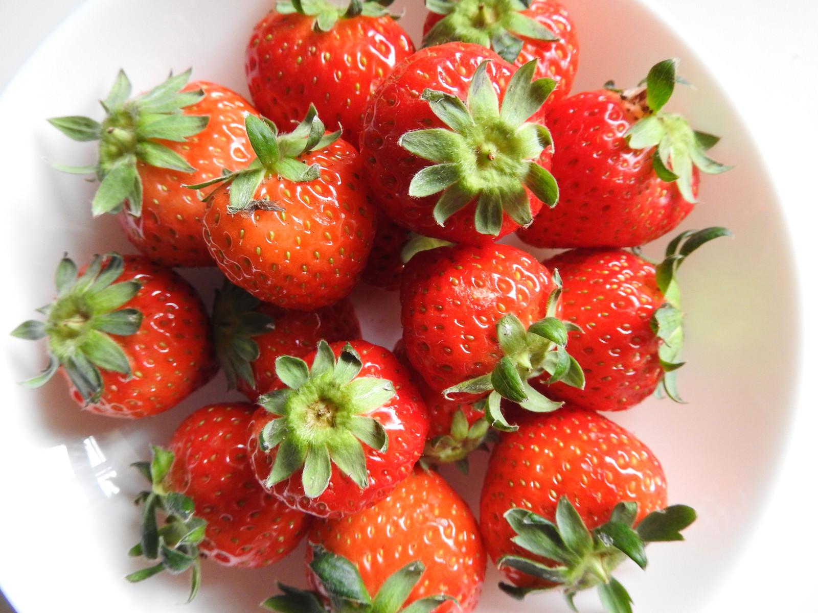 「皿に盛られたへた付きの苺」の写真