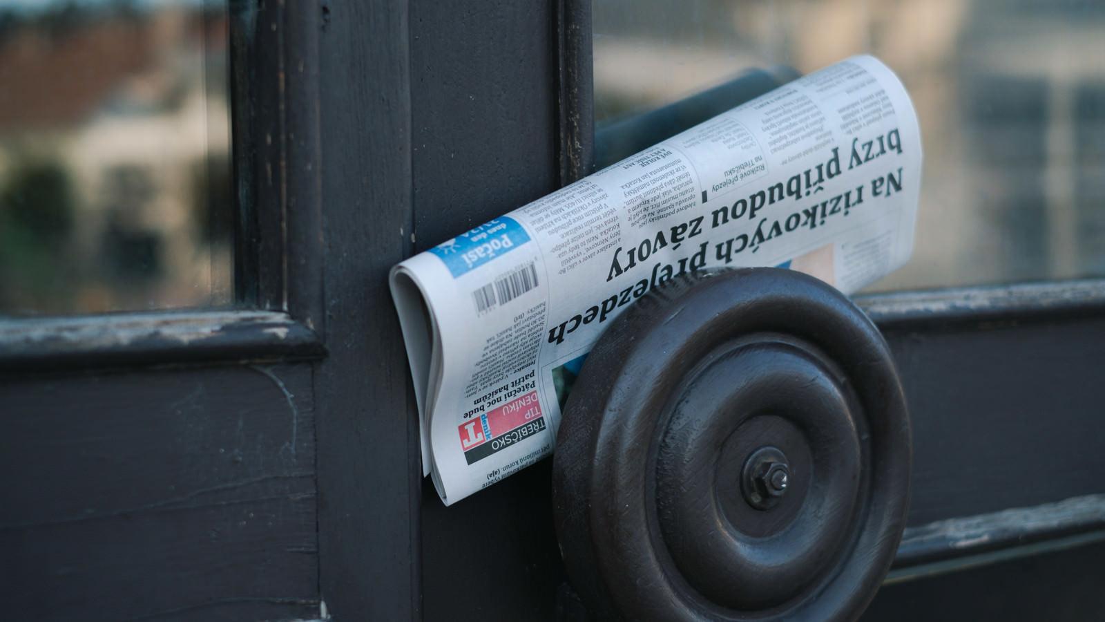 「取っ手に配達された新聞紙」の写真