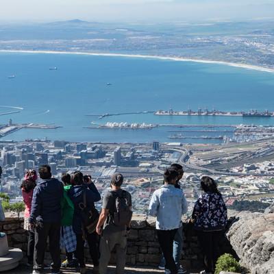 テーブルマウンテン頂上から見たケープタウン市内の街並みと観光客(南アフリカ)の写真