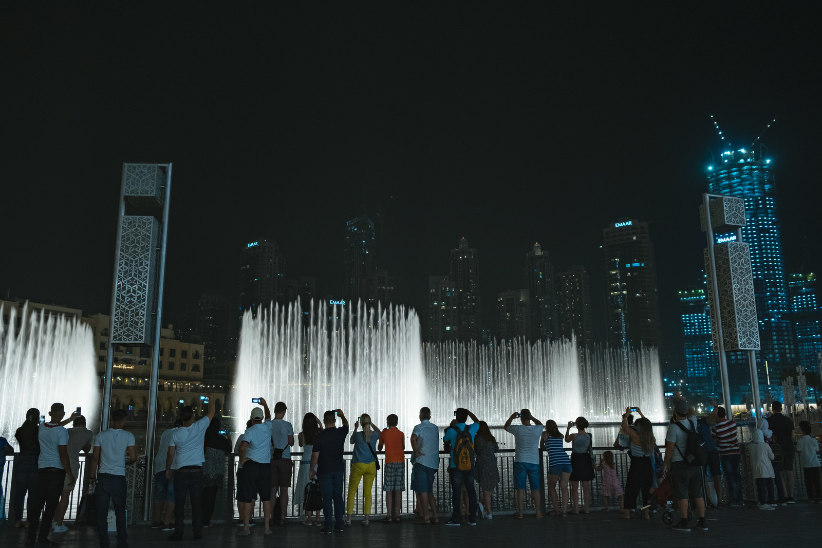 「高層ビルとライトアップされた噴水に群がる観光客」の写真