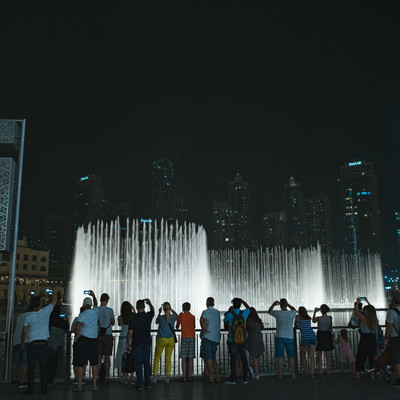 高層ビルとライトアップされた噴水に群がる観光客の写真