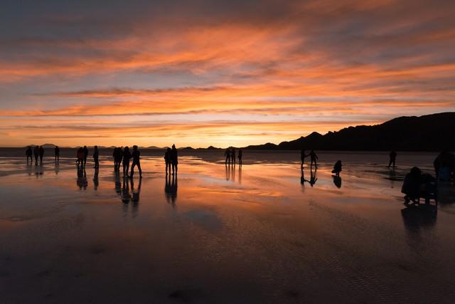 美しい夕暮れのウユニ塩湖と観光客のシルエットの写真