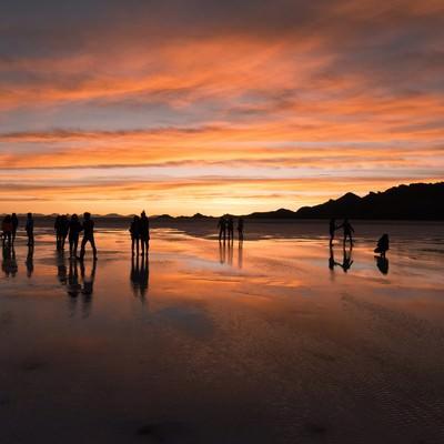 「美しい夕暮れのウユニ塩湖と観光客のシルエット」の写真素材