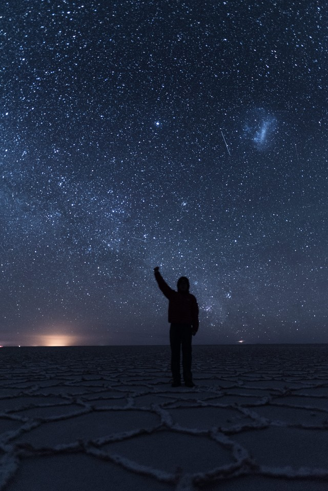 ウユニ塩湖の星空の下で手をあげる観光客の写真
