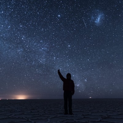 「ウユニ塩湖の星空の下で手をあげる観光客」の写真素材