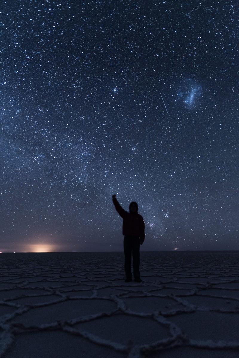 「ウユニ塩湖の星空の下で手をあげる観光客」の写真