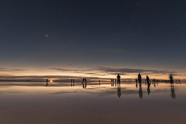 ウユニ塩湖の日没と星空を楽しむ観光客の写真