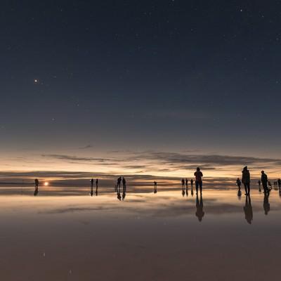 「ウユニ塩湖の日没と星空を楽しむ観光客」の写真素材