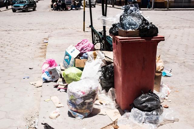 ゴミ箱から溢れ出す投棄物の写真