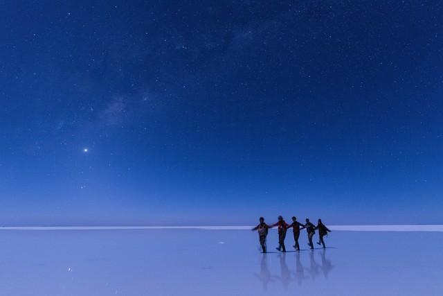 ウユニ塩湖で星空ツアーを楽しむ観光客の写真
