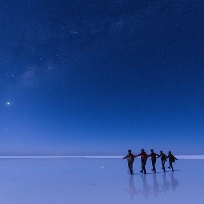 「ウユニ塩湖で星空ツアーを楽しむ観光客」の写真素材