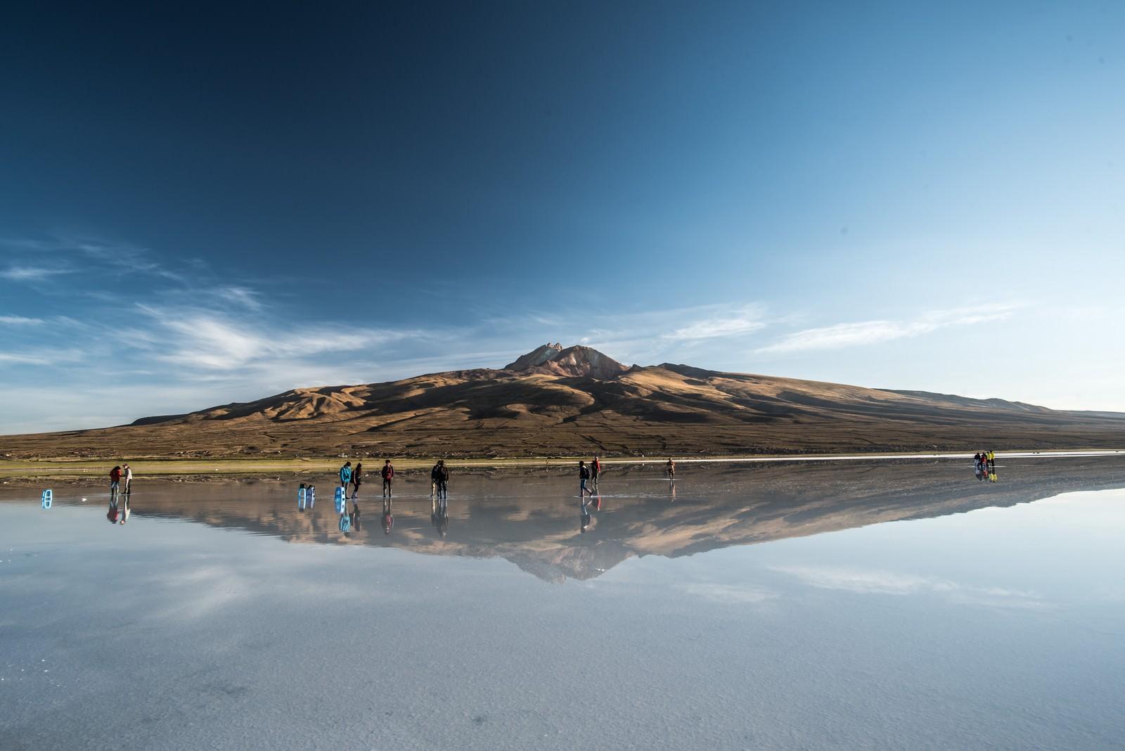「ウユニ塩湖に訪れた観光客と鏡のように映り込む山」の写真