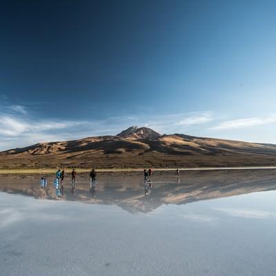 ウユニ塩湖に訪れた観光客と鏡のように映り込む山の写真