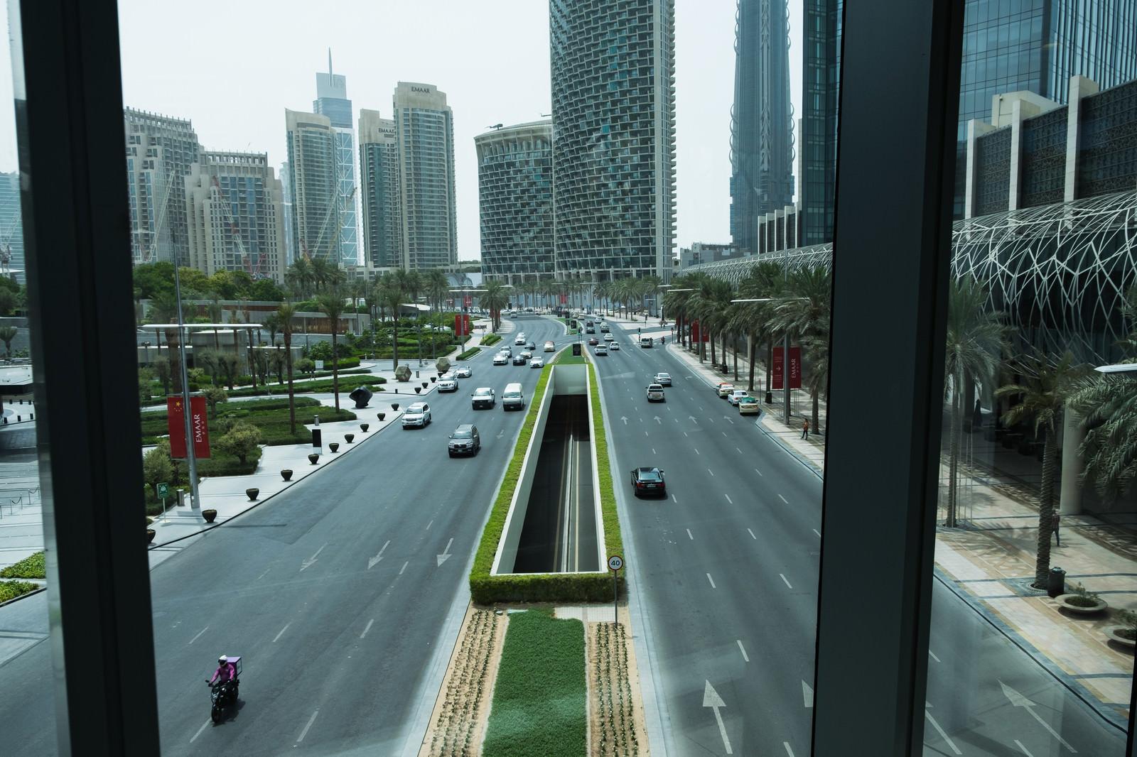 「高層ビル群へと続く道路を行き交う車(ドバイ)」の写真