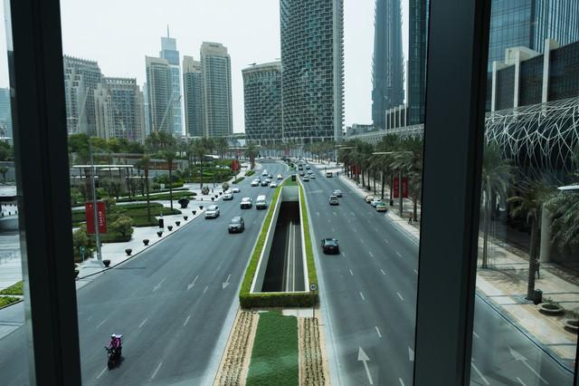 高層ビル群へと続く道路を行き交う車(ドバイ)の写真