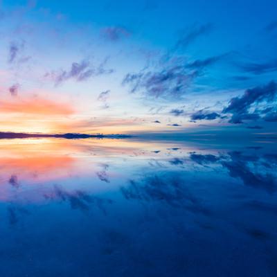 沈む夕日とグラデーションの夕焼け(ウユニ塩湖)の写真