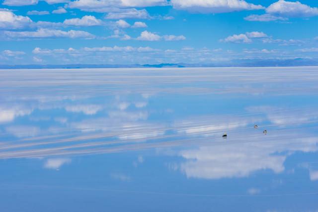 天空の鏡と呼ばれる雨季のウユニ塩湖を横断する車の写真