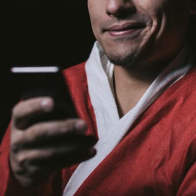 サンタコスイベントを調べる独身男性の写真