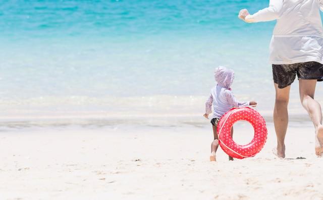美しい海で追いかけっこする親子の写真