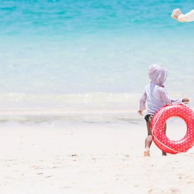 「美しい海で追いかけっこする親子」の写真素材