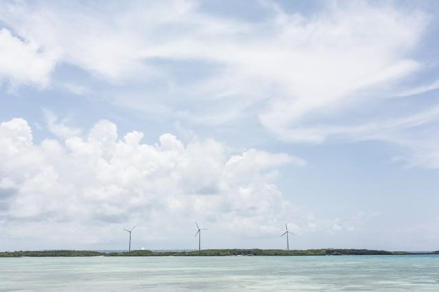 透き通る海と風力発電の写真